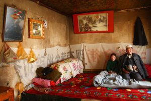 BMEHED Elderly Salar man on Kang bed-stove with his granddaughter, Xunhua Salar Autonomous County, Haidong, Qinghai, China